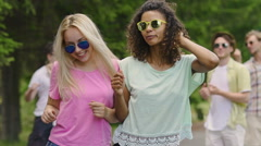 Two young happy women dancing to music at party, guys enjoying summer in park Stock Footage