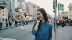 Busy street. Pretty woman talks on the phone, hangs up. People cross the road at Stock Footage