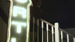 Well dressed young man walks down a set of stairs in a nightclub Stock Footage