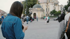 Busy street. Backview of a pretty woman walking, using smartphone. She flips her Stock Footage