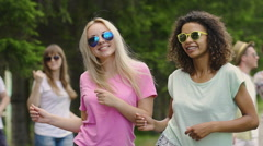 Couple of hot girls dancing with friends at open air festival, enjoying summer Stock Footage