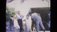 1966: two guys outside washing the driveway with a broom CATALINA, CALIFORNIA Stock Footage