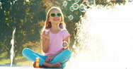 Fountain child is emotional. Girl blowing soap bubbles near fountain Stock Footage