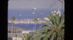 1966: sunny day on a beach with boats docked on the ocean as a small plane flies Stock Footage