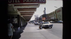 1966: lady walks down a sidewalk in a city on a busy street while cars pass by Stock Footage
