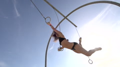 A woman in a black bikini swinging on the traveling rings at Santa Monica beach. Stock Footage