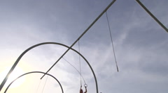 A young man swinging on the traveling rings at Santa Monica beach. Stock Footage