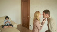 Boy is present at a quarrel parents. son of headphones plays in cell phone Stock Footage