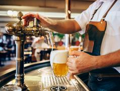 Bartender pouring the fresh beer in one of Czech traditional pubs Stock Photos