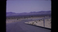 1966: a large highway with cars driving through the desert with mountains all Stock Footage