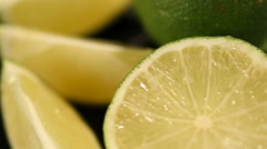 Fresh juicy limes cut in halves turning on stand, preparation of cocktails Stock Footage
