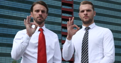 Serious Handsome Businessmen Looking Camera Hand Gestures Ok Sign Urban Scene Stock Footage