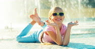 Child lying on fountain background at sunny day and waving hand Stock Footage