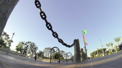 Skateboarder doing an ollie jumping trick over chains. Stock Footage