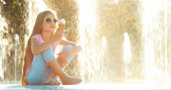 Girl 8 years old eating ice-cream on fountain background Stock Footage