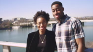 Portrait of an African American couple smiling on a waterfront in the city Stock Footage