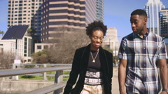 African American couple taking a walk along a city waterfront Stock Footage