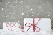 Gift, Cement Background With Snowflakes, Joyeux Noel Means Merry Christmas Stock Photos