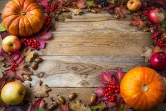 Frame of pumpkins, apples, acorns, berries and fall leaves on wooden backgrou Stock Photos