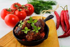 Meatballs with chili pepper and tomato served in cast iron skillet Stock Photos