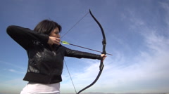 A female archer shooting targets with her bow and arrow. Stock Footage