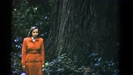 1952: a woman in an orange outfit standing next to a massive tree SAN FRANCISCO Stock Footage