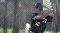 A young man practices baseball at the batting cages. Stock Footage