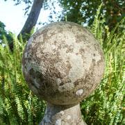 Stone sphere on a pedestal at a formal garden Stock Photos