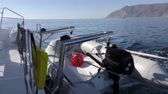 Looking aft of the catamaran a fully loaded and ready shore dinghy Stock Footage