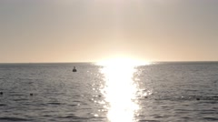 Sun burns the open ocean as the moored yacht bobs in the calm sea Stock Footage