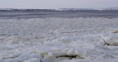 Tilt from ice choked river to blocks of frozen ice close Stock Footage