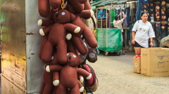 Vendor Draws Hand-cart with Toy-Bears along Trade District Stock Footage