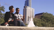Couple in front of city high rises, taking a picture together Stock Footage