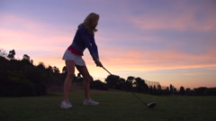 A woman teeing off while playing golf at sunset. Stock Footage