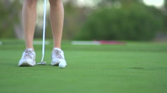 Close-up of a woman putting on the green while playing golf. Stock Footage