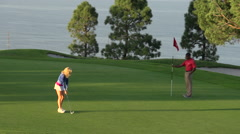 A woman putting on the green while playing golf. Stock Footage