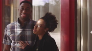 African American couple posing together in front of a red building Stock Footage