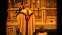 1964: boy genuflects before church altar while priest and acolyte pray RACINE Stock Footage