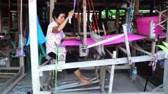 Thai weaver weaves silk fabric on wooden weaving loom machines Stock Footage
