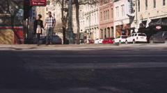 African American couple holding hands and walking across a street Stock Footage
