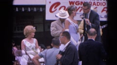1964: a woman wearing a sash on stage with two men in a beauty pageant RACINE Stock Footage