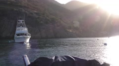 Large fishing yacht glows from the sun cresting the island Stock Footage
