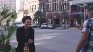 African American couple in the city taking cell phone pictures Stock Footage