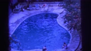 1962: people at a hotel enjoy the pool as they wade their toes  Stock Footage
