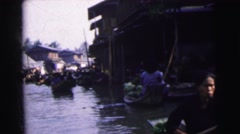 1962: vendors in small boats row down canal offering fruits and vegetables  Stock Footage