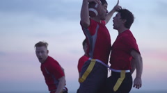 A group of guys playing flag football on the beach. Stock Footage