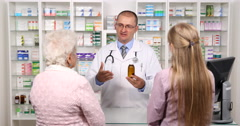 Young Old Female Pharmacy Customers Get Assistance Pharmacist Man Suggest Drug Stock Footage