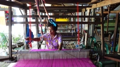 Thai weaver weaves silk fabric on wooden weaving loom machines Stock Footage