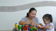 Girl playing wood blocks on the table with mother Stock Footage