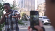 African American couple in the city taking cell phone pictures of each other Stock Footage